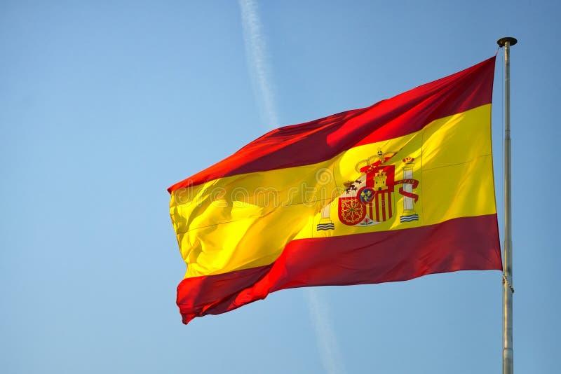 Flagga av Spanien på en mast som vinkar i vinden på en blå himmel royaltyfria foton