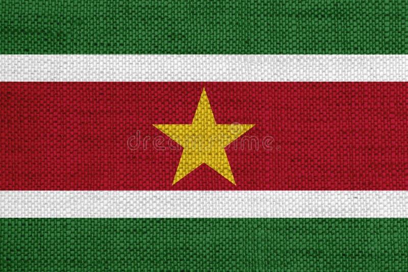 Flagga av Surinam på gammal linne arkivfoton