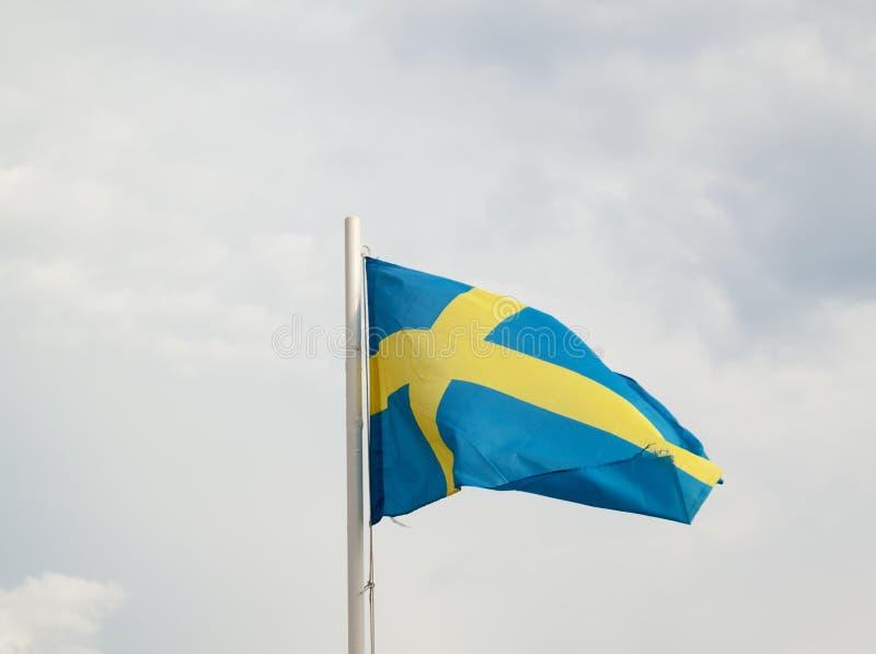 Flagga av Sverige p? en bl? himmel med molnbakgrund royaltyfri foto