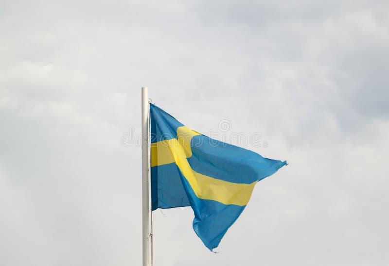 Flagga av Sverige p? en bl? himmel med molnbakgrund royaltyfria foton