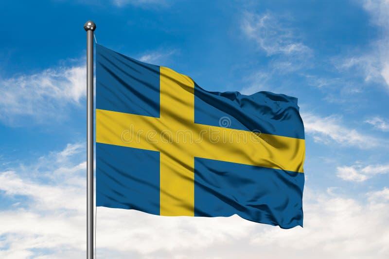 Flagga av Sverige som vinkar i vinden mot vit molnig blå himmel flag svensk royaltyfri fotografi