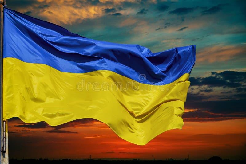 Flagga av Ukraina mot himmel på solnedgången royaltyfria bilder