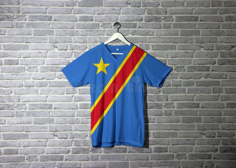 Flagga för Dr Congo på skjortan och hänga på väggen med tegelstenmodelltapeten royaltyfri foto