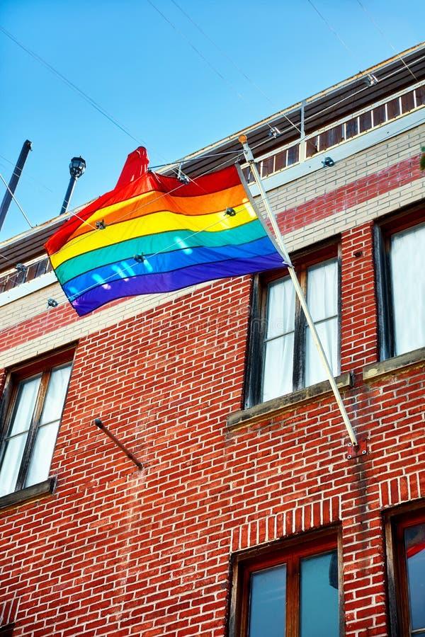 Flagga för glad stolthet för regnbåge som vinkar på flaggapolen av en tegelstenbuildi royaltyfri fotografi
