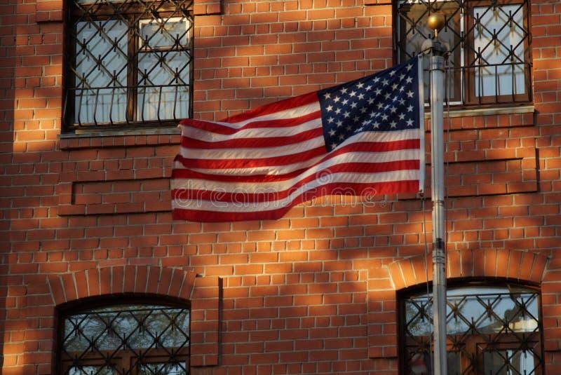 Flaggan är i harmoni med beståndsdelarna av fasaden fotografering för bildbyråer