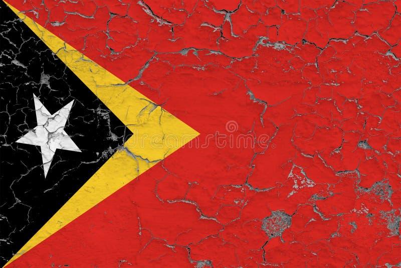 Flaggan av Östtimor målade på den spruckna smutsiga väggen Nationell modell p? tappningstilyttersida royaltyfri bild