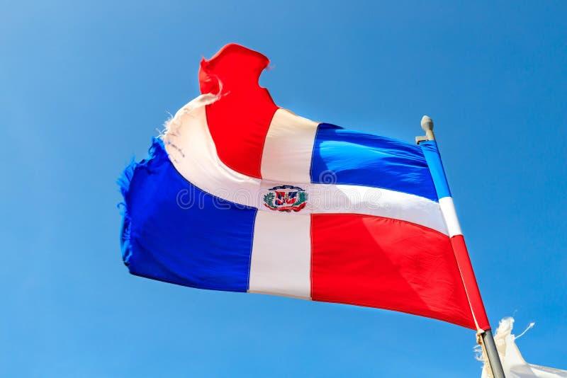 Flaggan av Dominikanska republiken vinkar för en blå himmel royaltyfria foton