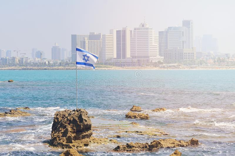 Flaggan av Israel mot bakgrunden av moderna Tel Aviv, th royaltyfri foto