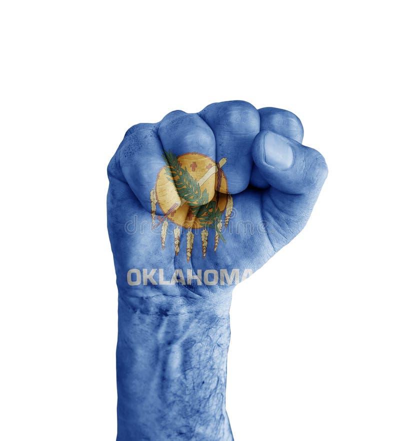 Flaggan av staten för USA Oklahoma målade på den mänskliga näven som seger royaltyfria bilder