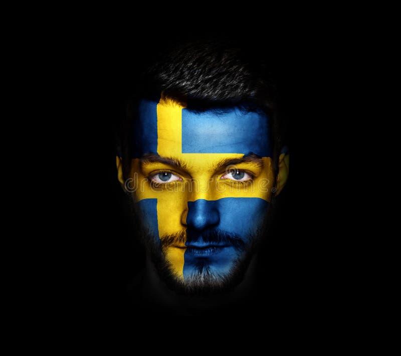 Flaggan av Sverige målade på en framsida av en man royaltyfria bilder