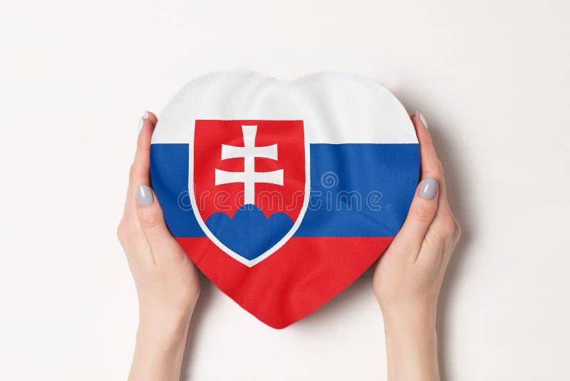 Flagge der Slowakei auf einem herzförmigen Karton in weiblichen Händen Weißer Hintergrund lizenzfreies stockfoto