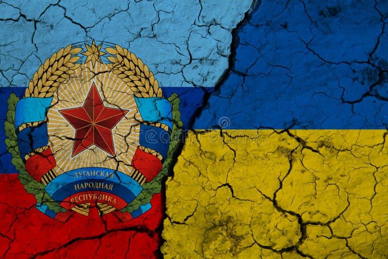 Flagge der Ukraine und der Volksrepublik Lugansk auf der zerrissenen Erde stockfotos