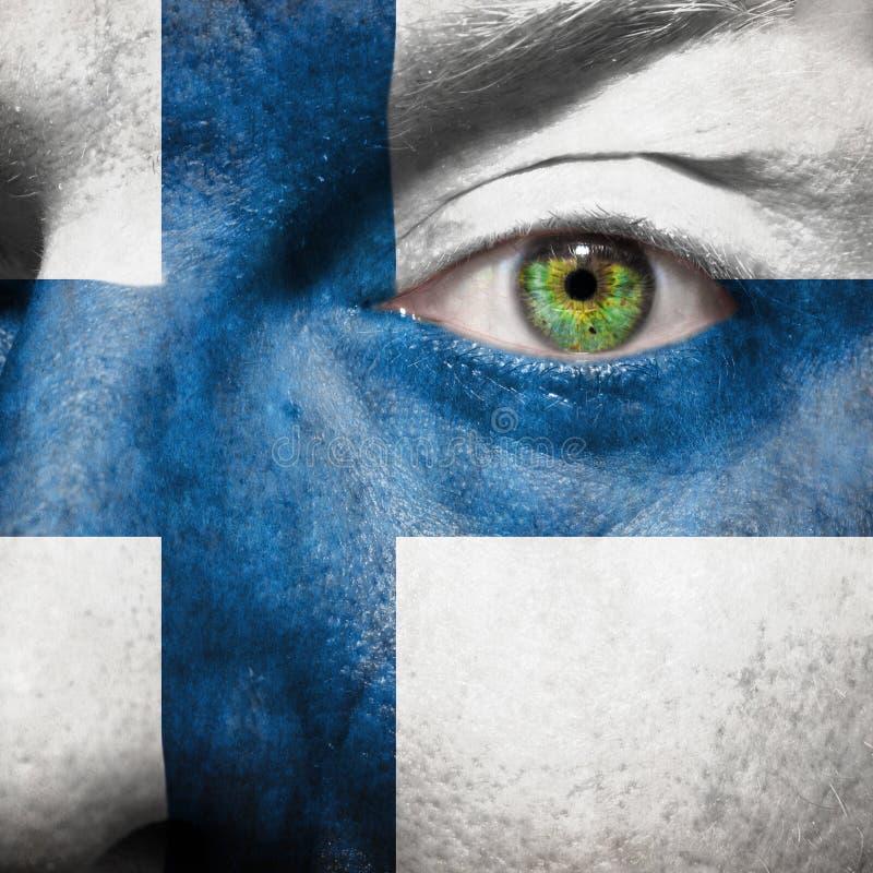 Flagge gemalt auf Gesicht mit grünem Auge, um Finnland-Unterstützung zu zeigen lizenzfreie stockfotos