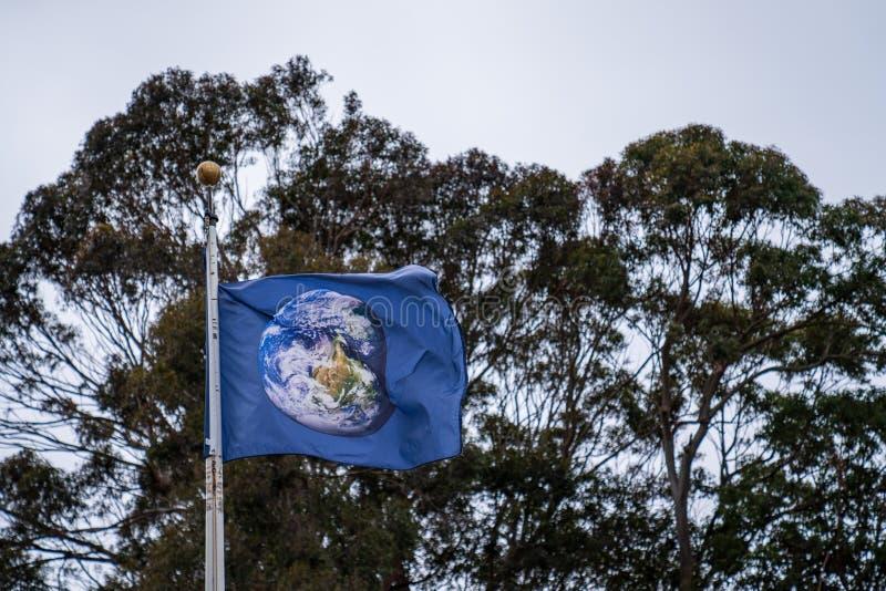Flagge mit dem Erdkugel-Satellitenbild, das in Wind auf bewölktem Himmel wellenartig bewegt lizenzfreie stockfotos