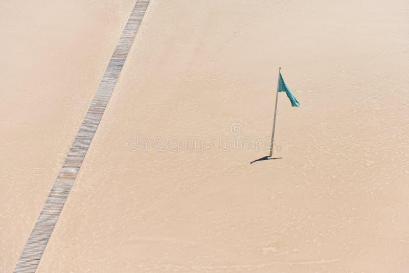Flagge und Bahn auf sandigem Strand lizenzfreie stockfotografie