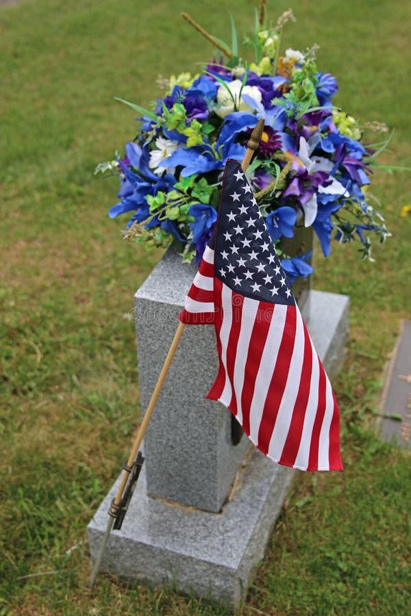 Flagge und Blumen auf Grundstein lizenzfreie stockfotografie