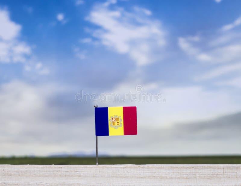 Flagge von Andorra mit beträchtlicher Wiese und blauem Himmel hinter ihm stockbilder