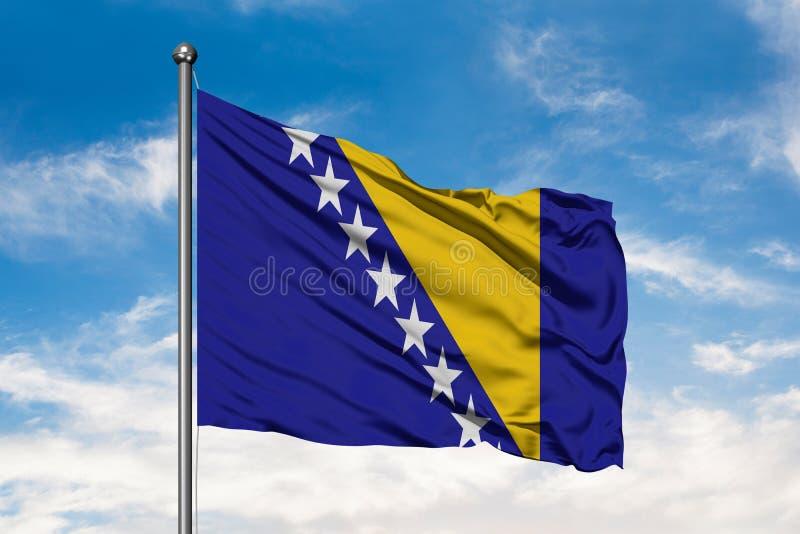 Flagge von Bosnien Herzegovina wellenartig bewegend in den Wind gegen weißen bewölkten blauen Himmel Bosnische Markierungsfahne stockfotos