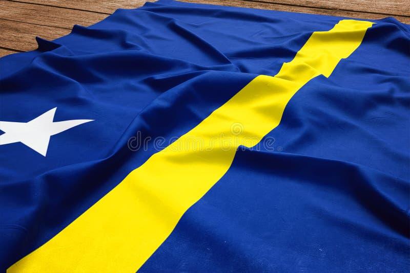 Flagge von Cura?ao auf einem h?lzernen Schreibtischhintergrund Draufsicht der Seidenflagge lizenzfreies stockbild