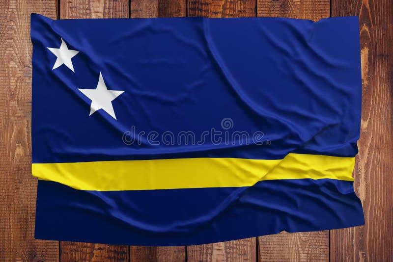 Flagge von Cura?ao auf einem Holztischhintergrund Geknitterte Draufsicht der Flagge lizenzfreie stockfotos