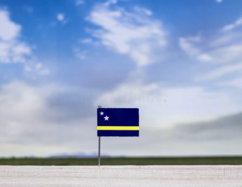Flagge von Curaçao mit beträchtlicher Wiese und blauem Himmel hinter ihm lizenzfreie stockfotografie