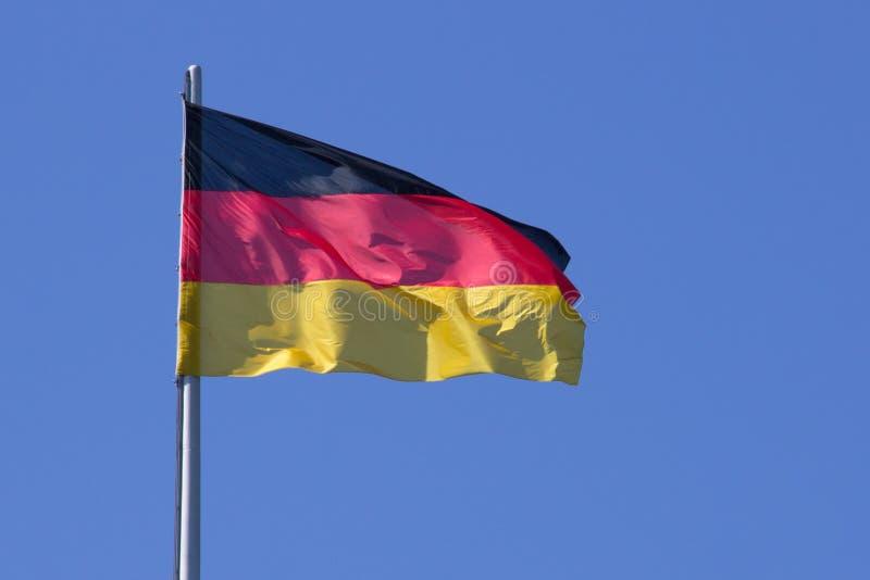 Flagge von Deutschland auf Fahnenmast gegen den blauen Himmel stockfotografie