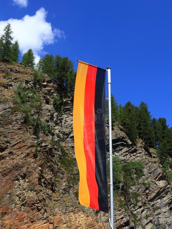 Flagge von Deutschland gegen Wald- und des blauen Himmelshintergrund stockbild