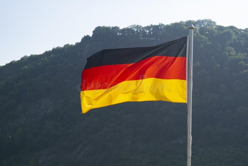 Flagge von Deutschland mit Bergen im Hintergrund stockfotos