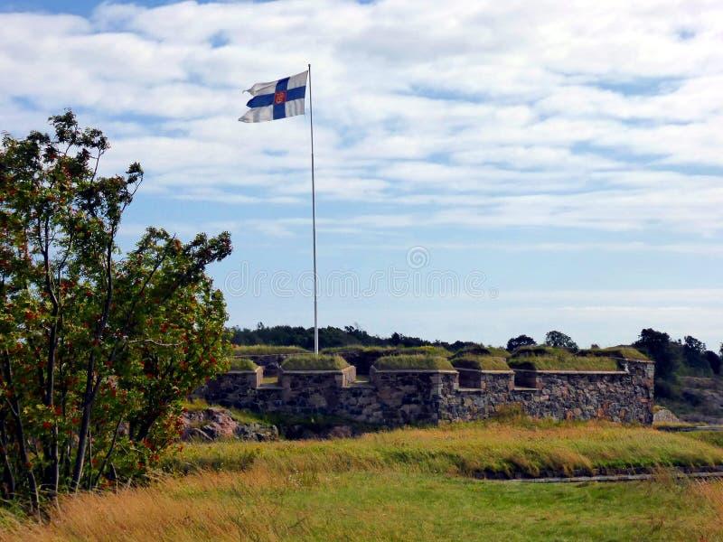 Flagge von Finnland in Suomenlinna-Seefestung auf den Inseln im Hafen von Helsinki lizenzfreie stockfotos