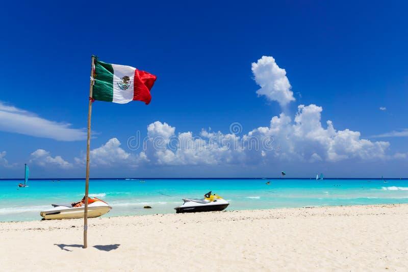 Flagge von Mexiko am Strand mit blauem bewölktem Himmel stockfotos