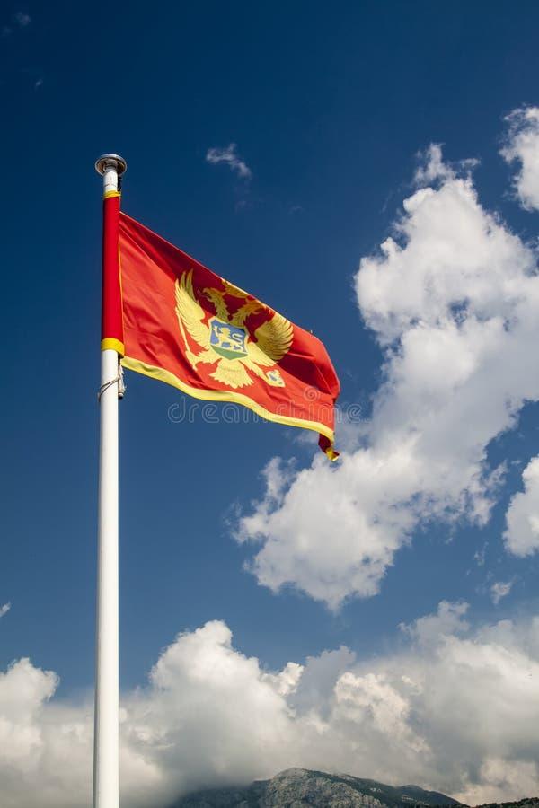 Flagge von Montenegro gegen blauen Himmel lizenzfreie stockfotos