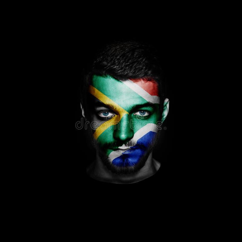 Flagge von Südafrika malte auf einem Gesicht eines Mannes stockfotografie