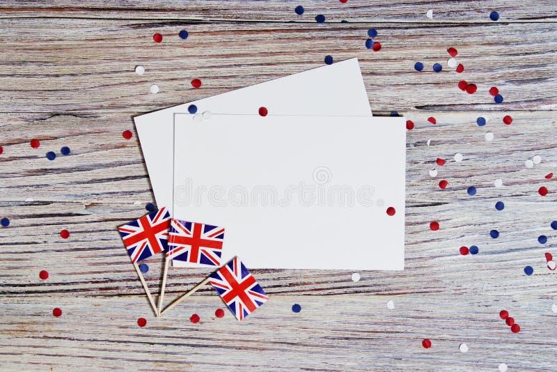 Flagge von Vereinigtem K?nigreich von Gro?britannien in der Hand auf Draufsicht des wei?en h?lzernen Hintergrundes Kopieren Sie P stockfotografie