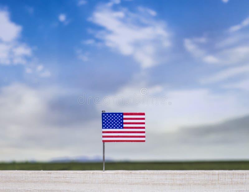 Flagge von Vereinigten Staaten mit beträchtlicher Wiese und blauem Himmel hinter ihm lizenzfreie stockfotografie