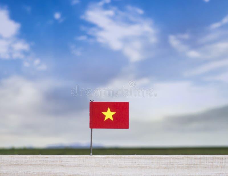 Flagge von Vietnam mit beträchtlicher Wiese und blauem Himmel hinter ihm stockfoto