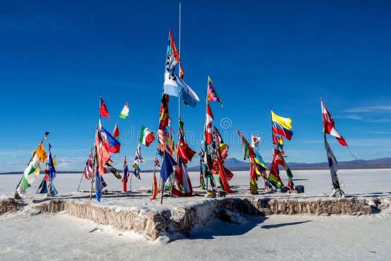 Flaggen des Weltfliegens außerhalb des Playa BLANCA-Salzhotels auf Salar de Uyuni lizenzfreie stockfotografie