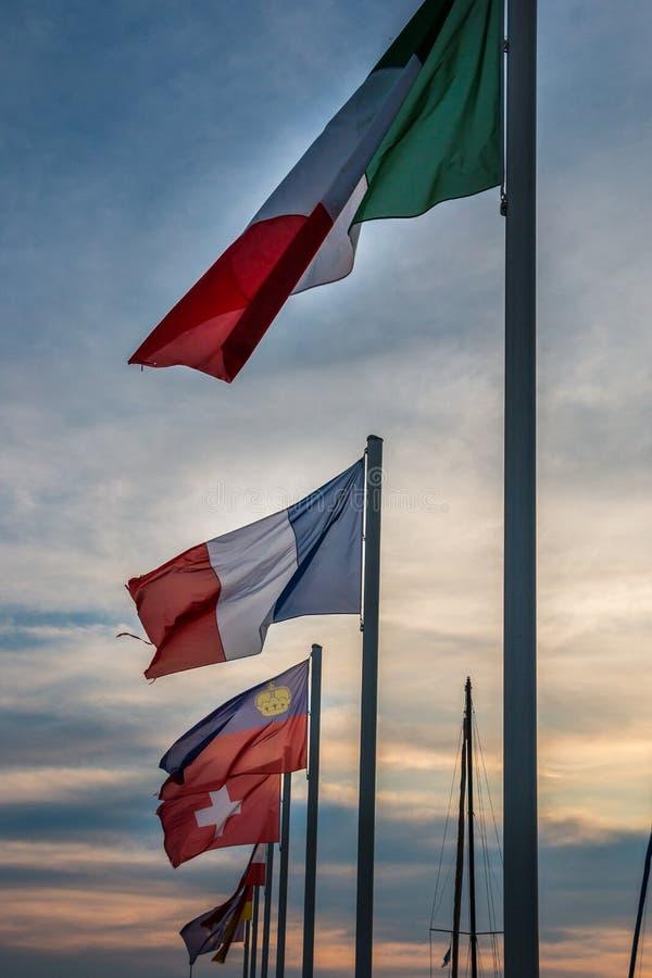 Flaggen verschiedener Länder und goldener Sonnenuntergang lizenzfreie stockfotografie