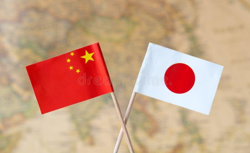 Flaggen von China und von Japan über der Weltkarte, Konzeptbild der politischen Beziehungen stockfotografie