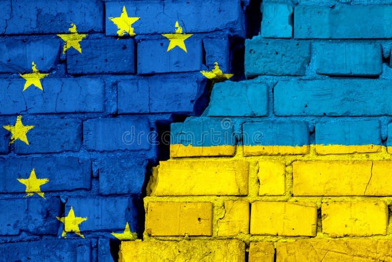 Flaggen von EU der Europäischen Gemeinschaft und von Ukraine auf der Backsteinmauer mit großem Sprung in der Mitte lizenzfreie abbildung