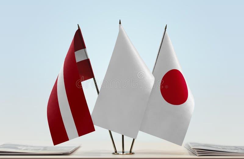 Flaggen von Lettland und von Japan lizenzfreie stockfotografie