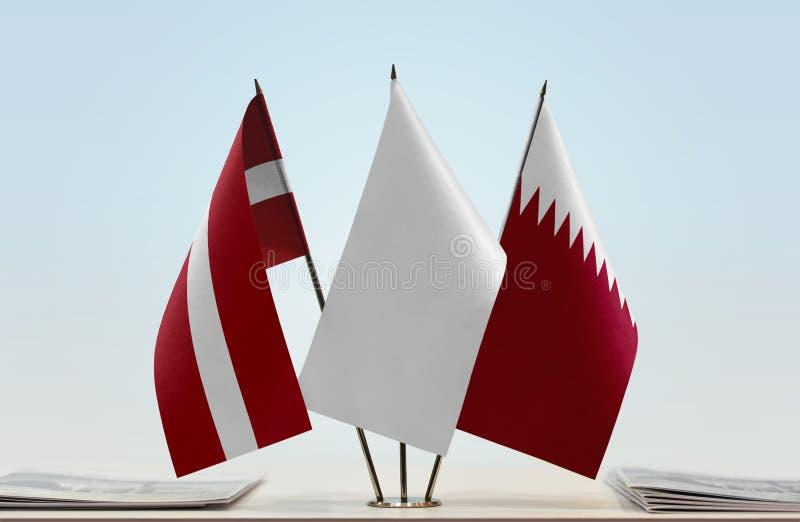 Flaggen von Lettland und von Katar lizenzfreie stockfotos