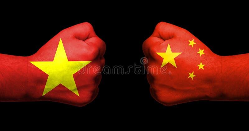 Flaggen von Vietnam und von China gemalt auf dem Gegenüberstellen zwei geballter Fäuste lizenzfreie stockfotografie