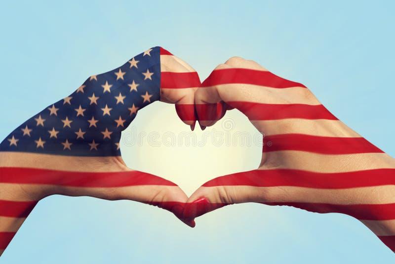 Flaggenmuster der Vereinigten Staaten von Amerika auf Leutehänden im Herzen formte Die Vereinigten Staaten von Amerika Staatsange stockfotos