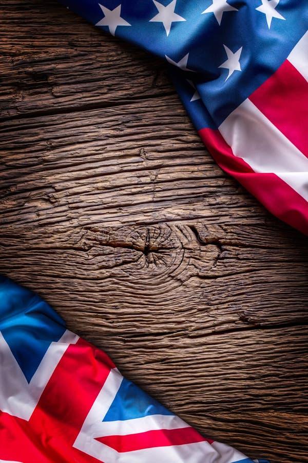 Flaggor av amerikanen och Förenade kungariket på lantlig ek stiger ombord UK- och USA flaggor tillsammans diagonalt arkivfoto