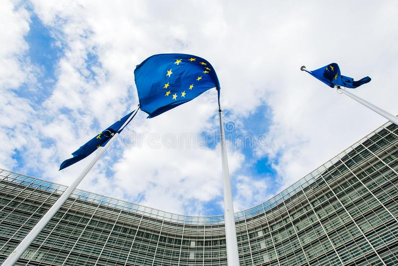 Flaggor av den europeiska unionen mot bakgrunden av Europeiska kommissionenbyggnaden Berlaymont i Bryssel, Belgien fotografering för bildbyråer