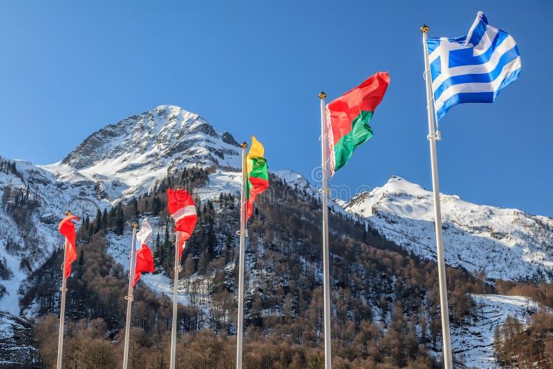 Flaggor av Grekland, Vitryssland, Litauen och andra länder vinkar i vinden som ett kamratskapsymbol på snöig bergmaximum och blåt arkivfoton