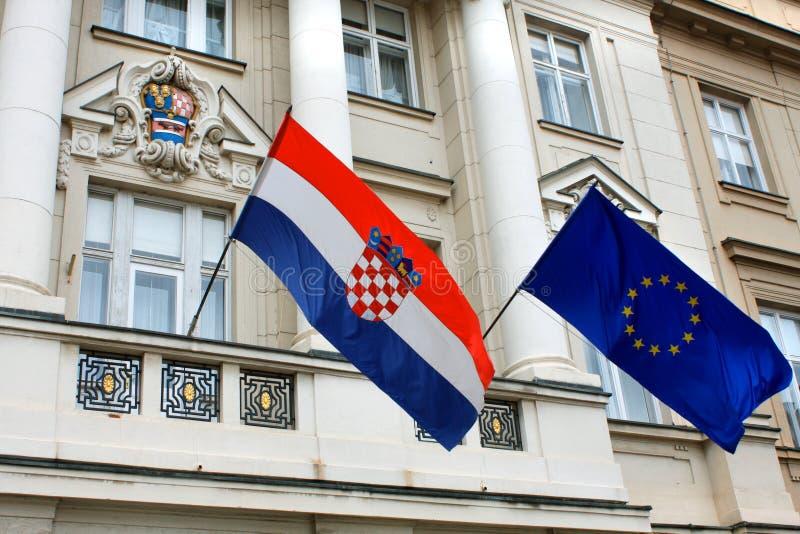 Flaggor av Kroatien och europeisk union mot fasaden av Croati arkivbilder