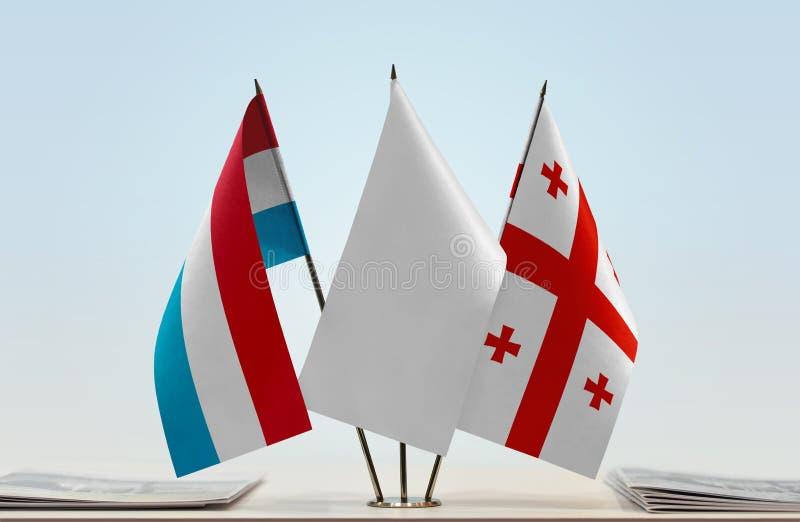 Flaggor av Luxembourg och Georgia royaltyfria bilder