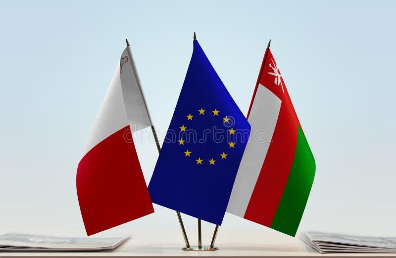 Flaggor av Malta EU och Oman arkivfoto