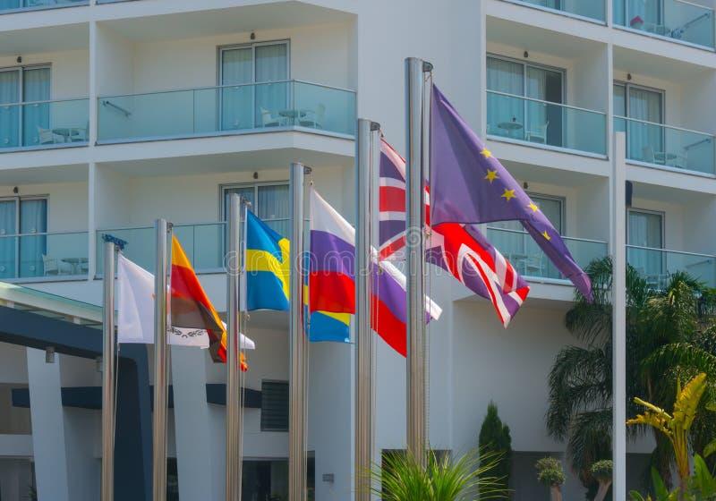 Flaggor av olika länder framme av hotellet i Ayia Napa i Cypern royaltyfri fotografi